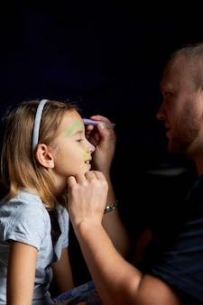 Filha e pai pintam uma cara, se divertindo