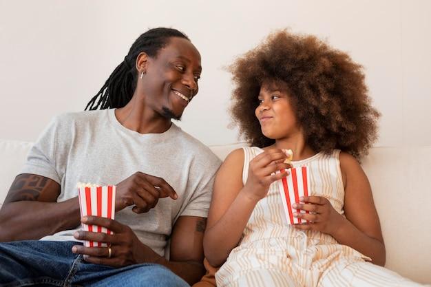 Filha e pai relaxando em casa assistindo filmes