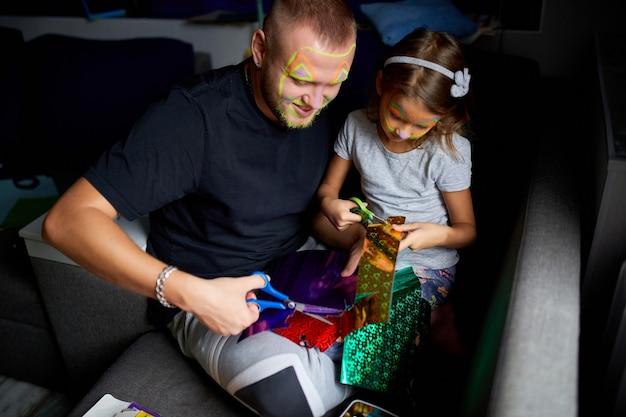 Filha e pai se divertindo fazendo artesanato juntos em casa no sofá, cortando um papel com tesoura, luz negra, dia dos pais, família.