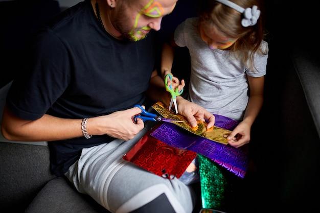 Filha e pai se divertindo fazendo artesanato juntos em casa no sofá