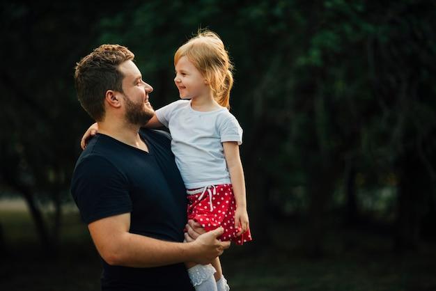 Filha e pai sorrindo um para o outro