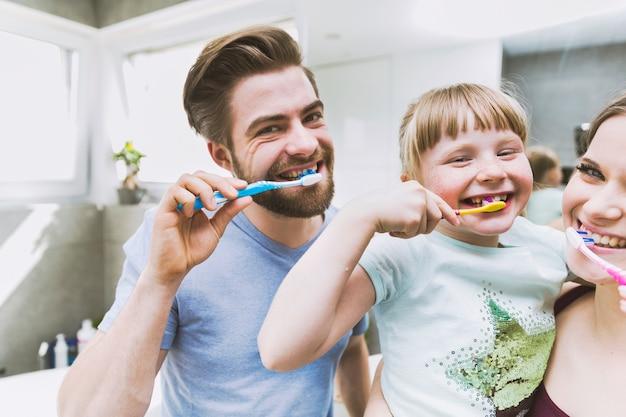 Filha e pais escovando os dentes