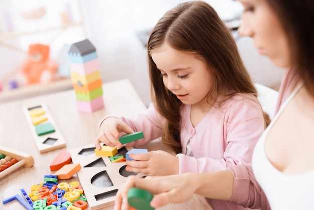 Filha estão brincando com figuras geométricas.