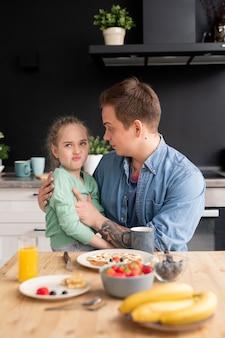 Filha exigente sentada nos joelhos do pai fazendo careta enquanto se recusa a comer o café da manhã feito pelo pai