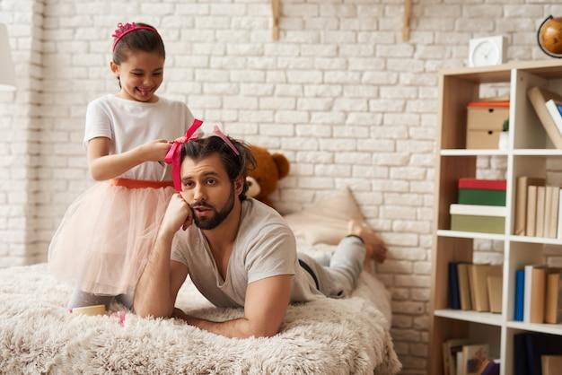 Filha fazendo penteados para o pai no quarto