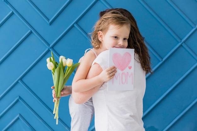 Filha feliz abraçando sua mãe com segurando flores e cartão contra o pano de fundo azul