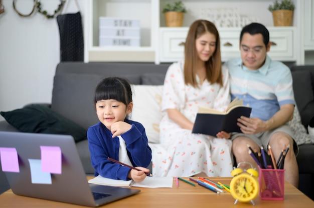 Filha feliz asiática está usando laptop para estudar online através da internet, enquanto os pais estão sentados no sofá em casa. conceito de e-learning