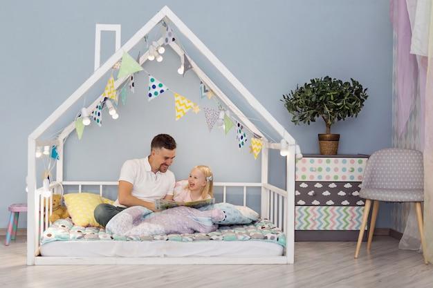 Filha feliz com seu pai bonito sorrindo enquanto lê um livro na cama de giro casa branca