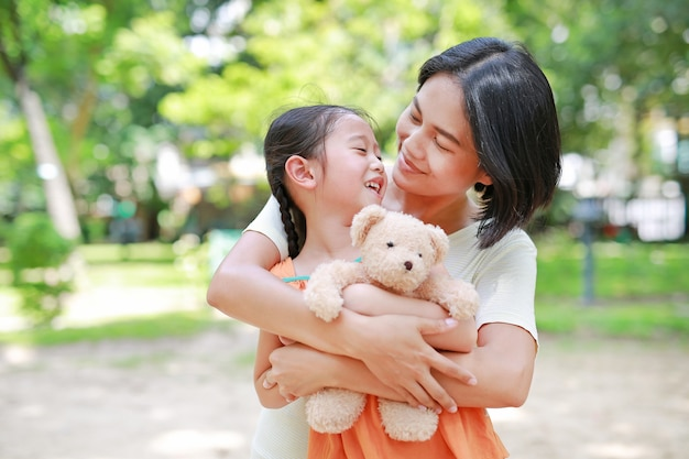 Filha feliz do afago da mamã e boneca do urso de peluche do aperto no jardim.