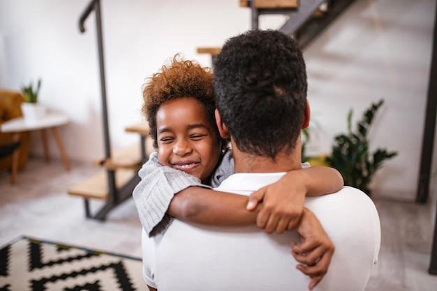 Filha feliz que abraça o pai em casa.