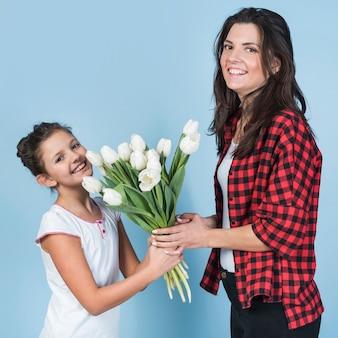 Filha fofa dando tulipas brancas para a mãe