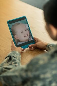 Filha fofa e sorridente. perto de uma mulher em um bate-papo por vídeo com sua linda filha sorridente