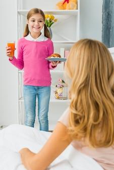 Filha fofa segurando o croissant na placa para a mãe na cama Foto gratuita