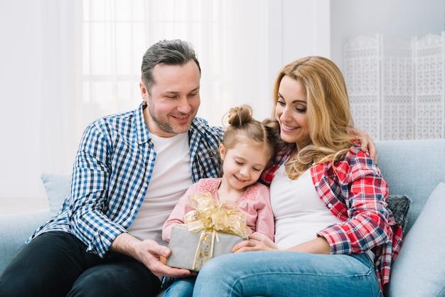 Filha fofa segurando presente com sua mãe e pai