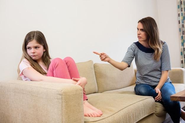 Filha ignorando sua mãe após uma discussão na sala de estar