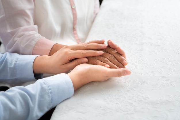 Filha incentivar mãe, jovens com idade segurando a mão de mulher velha, conceito de dia das mães