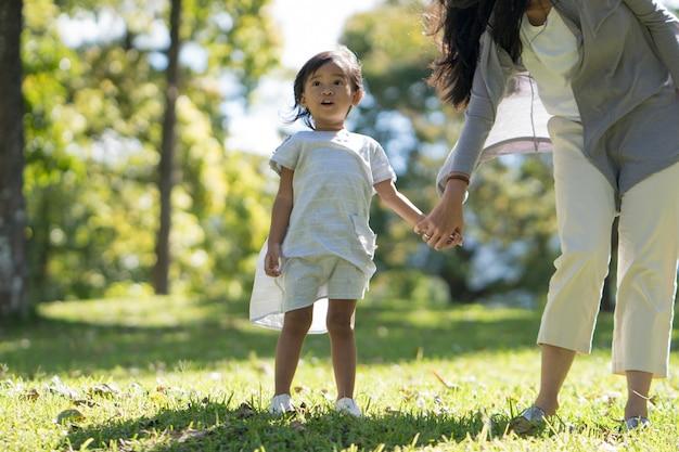 Filha jovem feliz com a mãe no parque