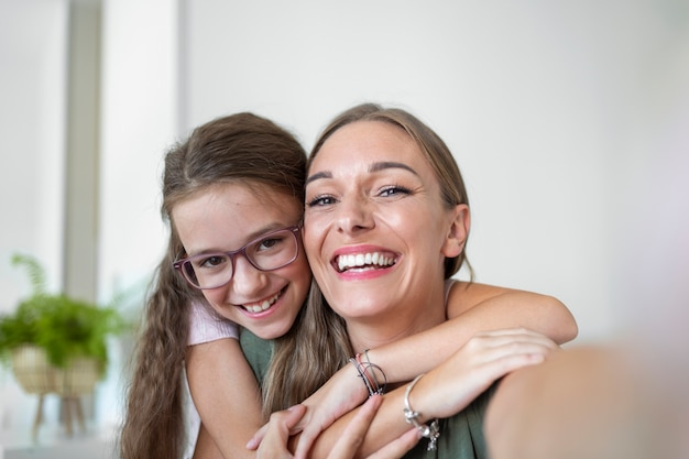 Filha jovem mãe enfrenta webcam close-up vista. garota adorável criança usando smartphone, se divertir com a irmã mais velha fazendo fotos de selfie, vloggers gravam novo vlog, aproveite o conceito de atividade engraçada