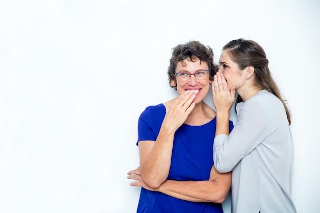 Filha jovens e seniores compartilhando de segredos mãe