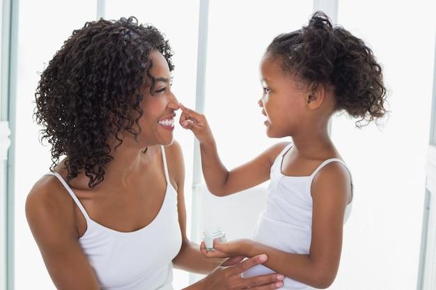 Filha linda colocando creme para o rosto no nariz de mães