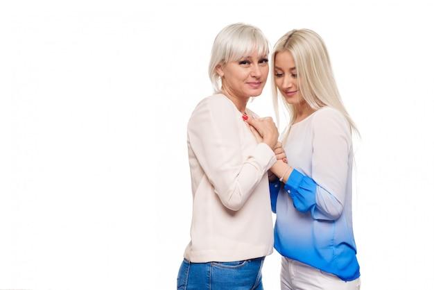 Filha loura adolescente e mãe madura no abraço branco