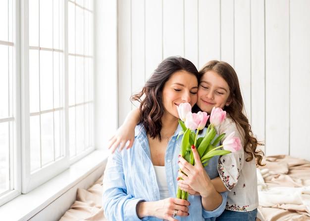 Filha mãe abraça com tulipas
