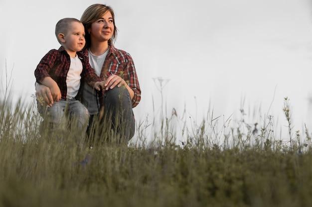 Filha mãe e bebê sentada em um gramado verde e sorrindo.