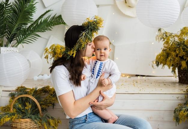 Filha mãe e bebê sentam-se com buquês de mimosa e a mãe beija a filha. dia das mães