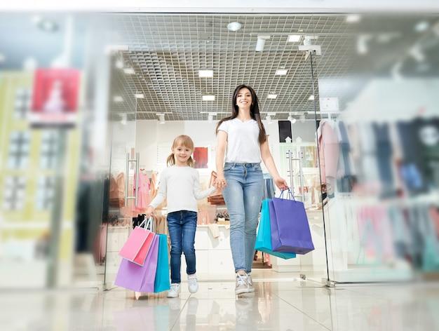 Filha, mantendo a mão da mãe e saindo da loja