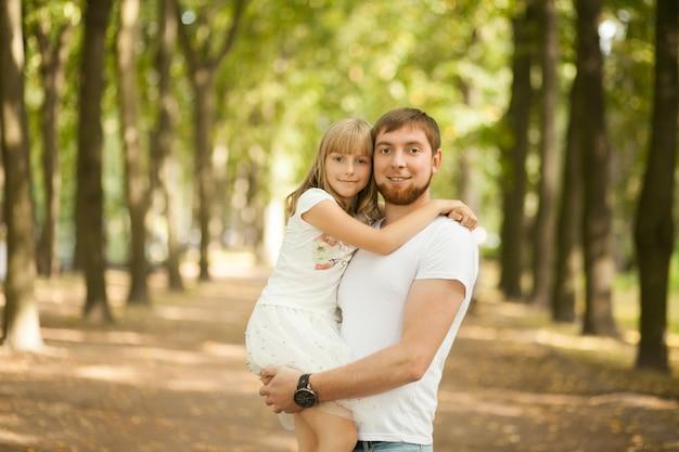 Filha nos braços do pai no parque de verão.
