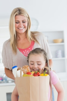 Filha olhando para bolsa de compras com a mãe assistindo