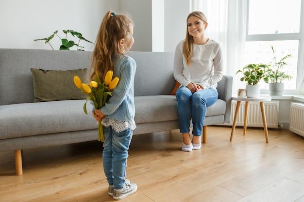 Filha pequena com buquê de flores amarelas parabeniza sua mãe sorridente