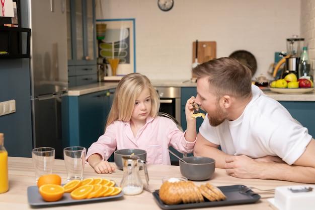 Filha pequena com longos cabelos loiros alimentando o pai com muesli enquanto ambos estão sentados à mesa tomando café da manhã