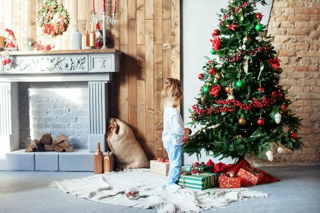 Filha pequena decora a árvore de natal. o conceito de chr