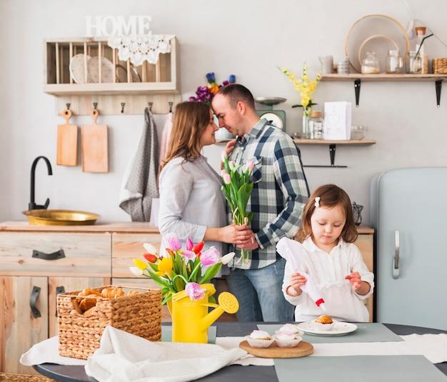 Filha pequena fazendo bolinho perto de pais com flores