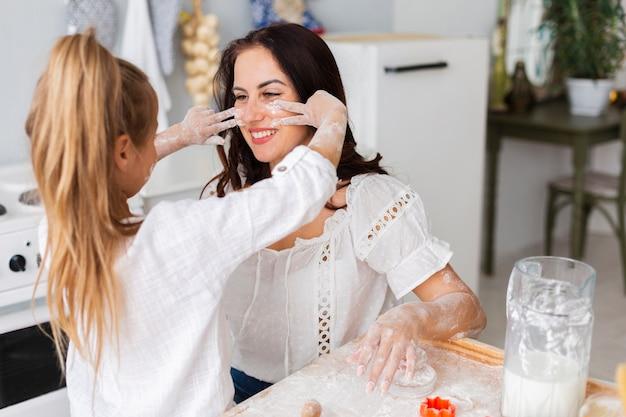 Filha pintando com farinha o rosto da mãe