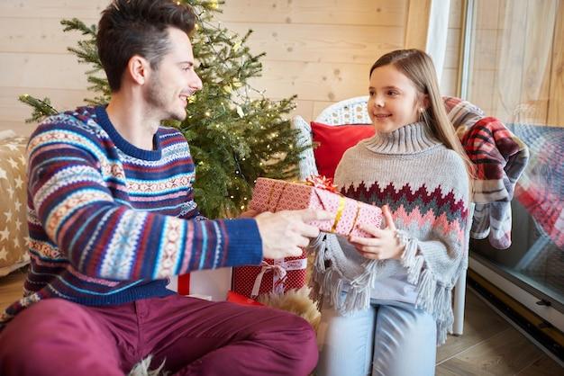 Filha recebendo presente de natal do pai