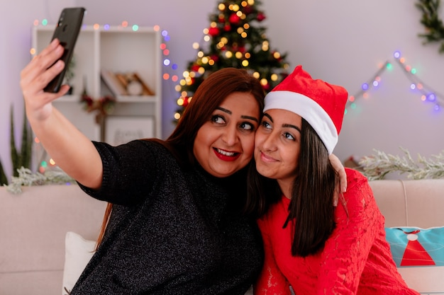 Filha satisfeita com chapéu de papai noel e mãe tirando uma selfie olhando para o telefone, sentada no sofá, aproveitando o natal em casa