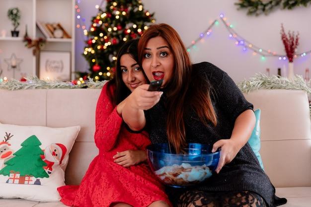 Filha satisfeita sentada no sofá com a mãe animada segurando o controle remoto da tv e uma tigela de batatas fritas, aproveitando o natal em casa