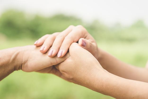 Filha segurando a mão da mãe dela