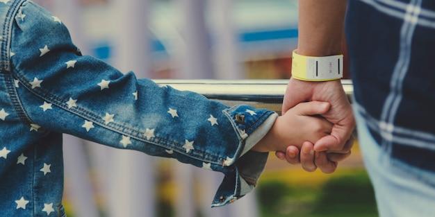 Filha segurando a mão do pai enquanto caminhava