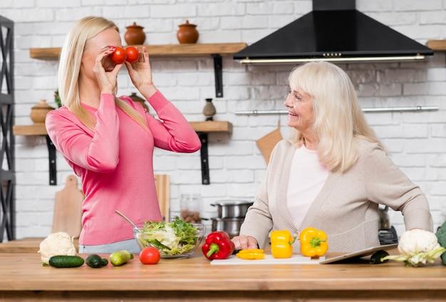 Filha segurando tomates como binóculos