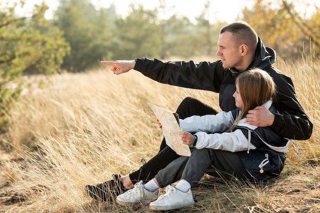 Filha segurando um mapa e pai mostrando a direção