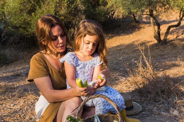 Filha sentada no colo da mãe, segurando o alho-poró no campo
