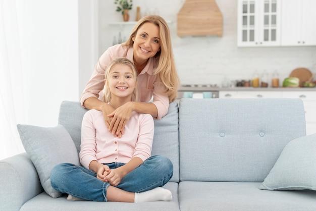 Filha sentada no sofá, abraçado pela mãe