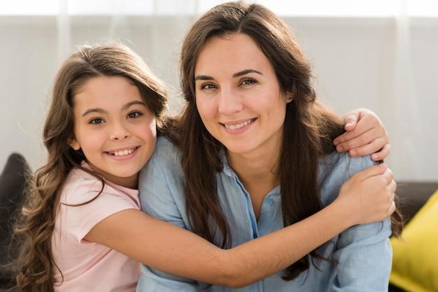 Filha sorridente, abraçando a mãe na sala de estar