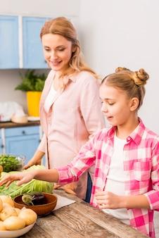 Filha sorridente ajudando a mãe na cozinha