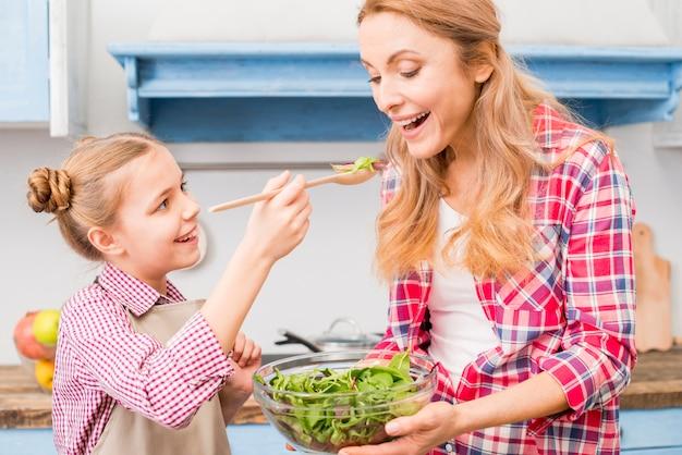 Filha sorridente, alimentando a salada para a mãe na cozinha