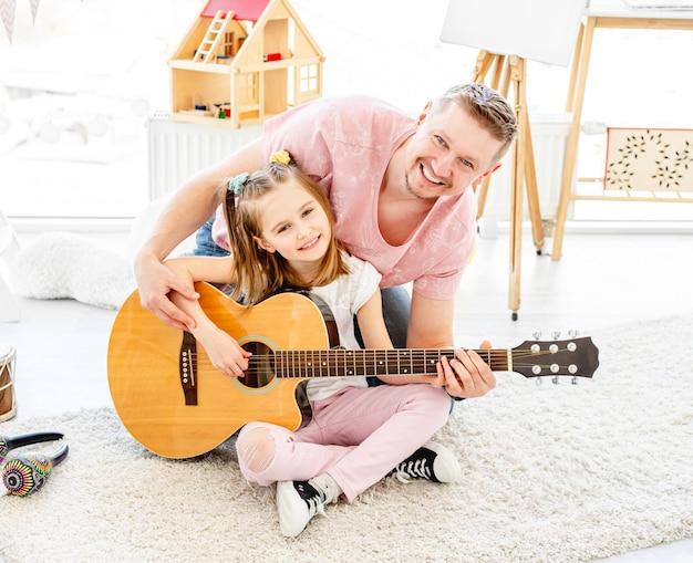 Filha sorridente com o pai tocando violão