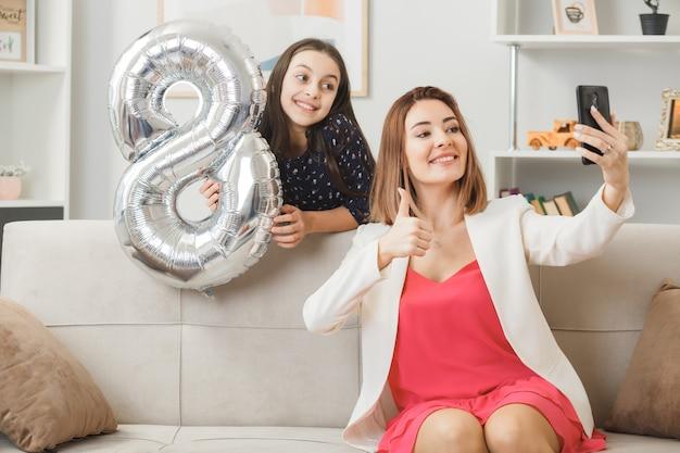 Filha sorridente, em pé atrás do sofá, segurando o balão número oito, mãe sentada no sofá, tirar uma selfie no dia da mulher feliz na sala de estar